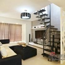 一进门是木制的鞋柜和白色雕花的玄关设计。玄关设计出来就是客厅设计旁边有黑色的螺旋楼梯上二楼。