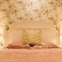 床头背景墙以碎花壁纸来装饰,白色木床透着清新与典雅。